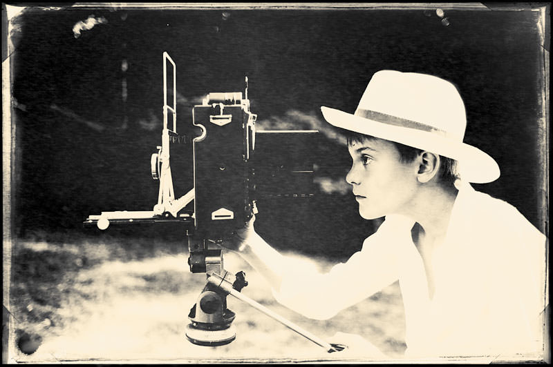 art photography - portrait photograph of young boy taking photographs with large format camera