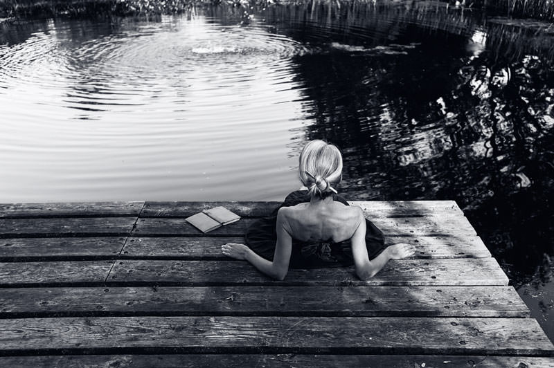 fine art photographer - woman resting by the water